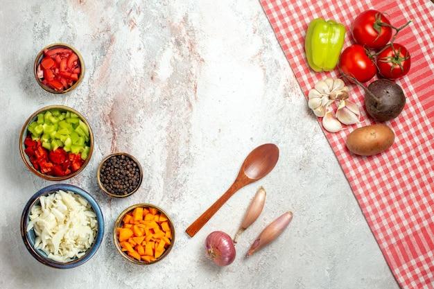 Vue de dessus des légumes frais avec du poivre tranché sur l'espace blanc