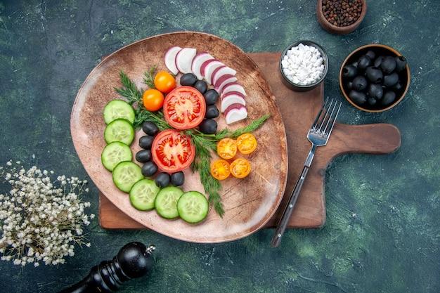 Vue de dessus de légumes frais hachés dans une assiette brune sur une planche à découper en bois olives dans un bol fleur d'ail sel sur fond de couleurs mélangées