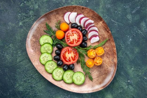 Vue de dessus des légumes frais hachés olives kumquats dans une assiette brune sur fond de couleurs mélangées noir vert