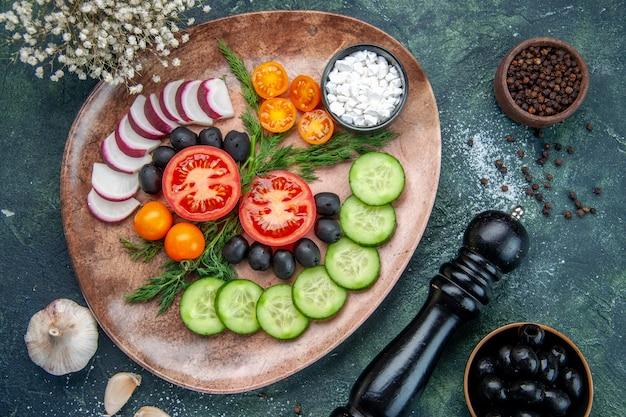 Vue de dessus des légumes frais hachés olives sel dans une assiette brune et fleur d'ail marteau de cuisine sur fond de couleurs mélangées noir vert
