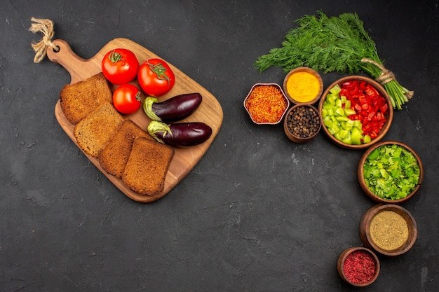 Vue de dessus des légumes frais avec des miches de pain noir et des assaisonnements sur la surface sombre des aliments de pain de repas de salade