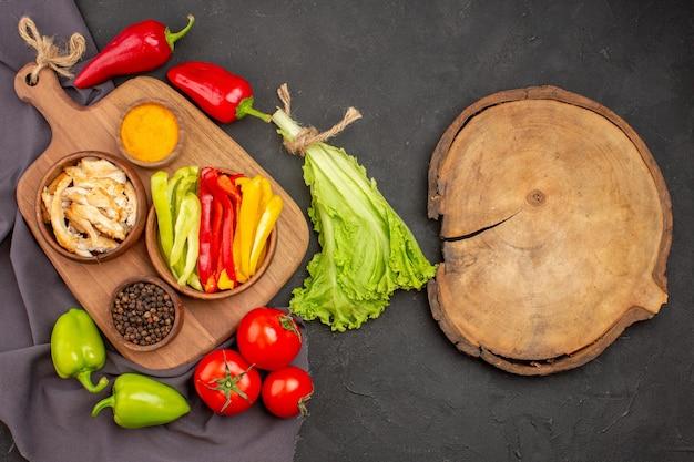 Vue de dessus des légumes frais mûrs avec assaisonnements sur fond noir