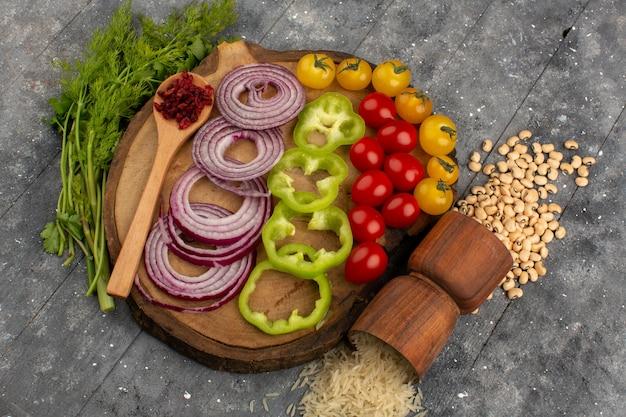Vue de dessus des légumes frais oignons émincés poivron vert et autres légumes sur le sol gris