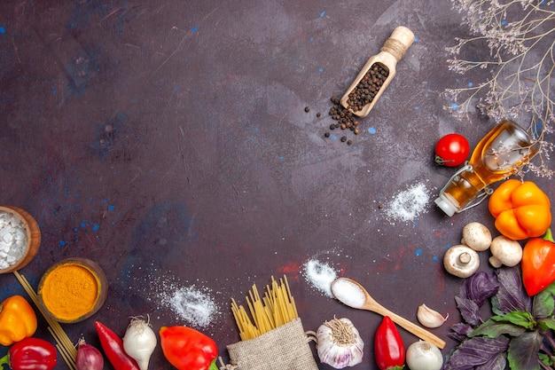 Vue de dessus des légumes frais avec des pâtes crues sur un repas sain de salade de surface sombre