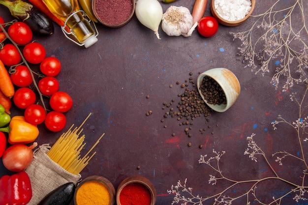 Vue de dessus des légumes frais avec des pâtes italiennes crues et des assaisonnements sur l'espace sombre