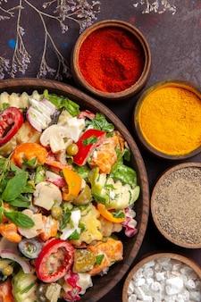 Vue de dessus de légumes frais. salade avec différents assaisonnements sur fond noir