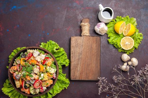 Vue de dessus de légumes frais. salade avec tranches de citron et salade verte sur fond noir