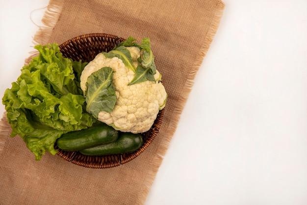 Vue de dessus de légumes frais tels que le chou-fleur de laitue et les concombres sur un seau sur un sac en tissu sur un fond blanc avec copie espace