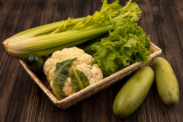 Vue de dessus de légumes frais tels que la laitue de céleri et le chou-fleur sur un seau avec des courgettes isolé sur un fond en bois