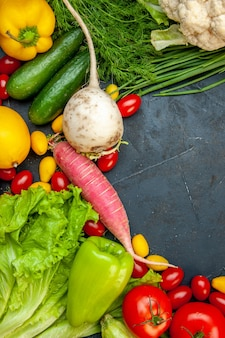 Vue de dessus légumes frais tomates cerises cumcuat chou-fleur radis oignon vert persil concombres poivrons tomates espace libre