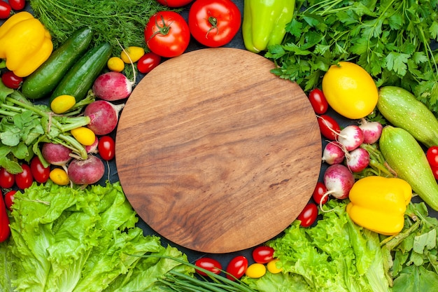 Vue de dessus légumes frais tomates laitue radis citron courgettes persil tomates cerises planche de bois ronde au centre sur une surface sombre