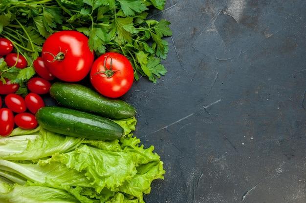 Vue de dessus légumes frais tomates persil concombres laitue tomates cerises sur une surface sombre avec copie place