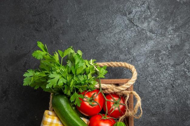 Vue de dessus des légumes frais, tomates rouges, concombres et courges avec des verts sur une surface gris foncé