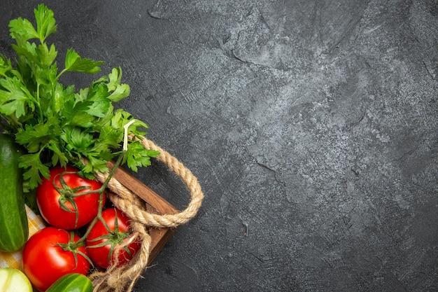 Vue de dessus des légumes frais, tomates rouges, concombres et courges avec des verts sur la surface grise