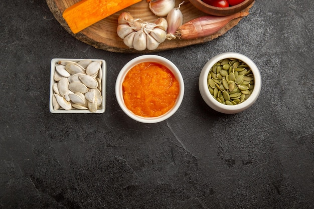 Vue de dessus des légumes frais avec des tranches de citrouille et de l'ail sur fond gris couleur des graines salade mûre fraîche