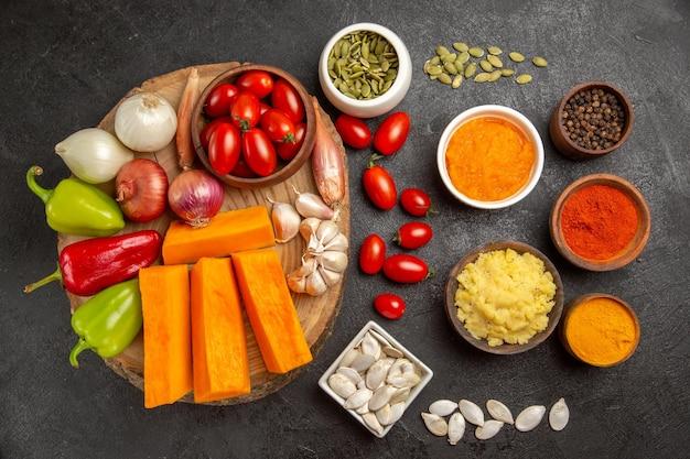 Vue de dessus des légumes frais avec des tranches de citrouille et de l'ail sur fond gris graine de couleur salade mûre fraîche