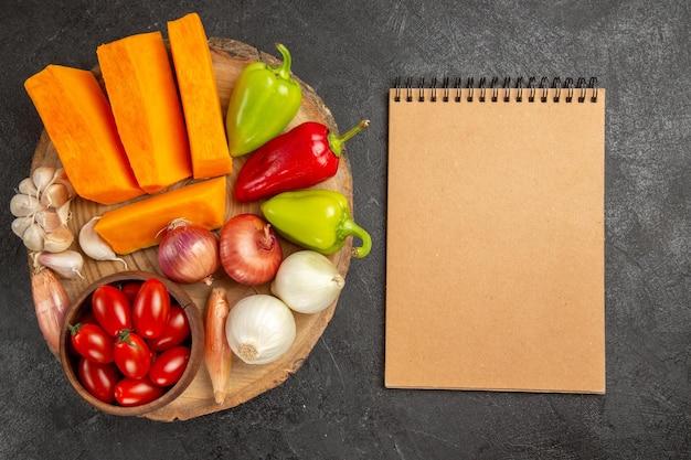 Vue de dessus des légumes frais avec des tranches de citrouille sur fond gris foncé couleur mûre fraîche