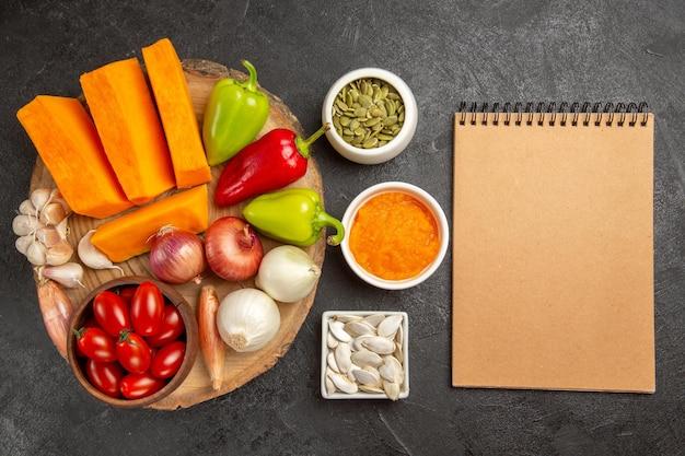 Vue de dessus des légumes frais avec des tranches de citrouille sur fond gris salade mûre de couleur fraîche