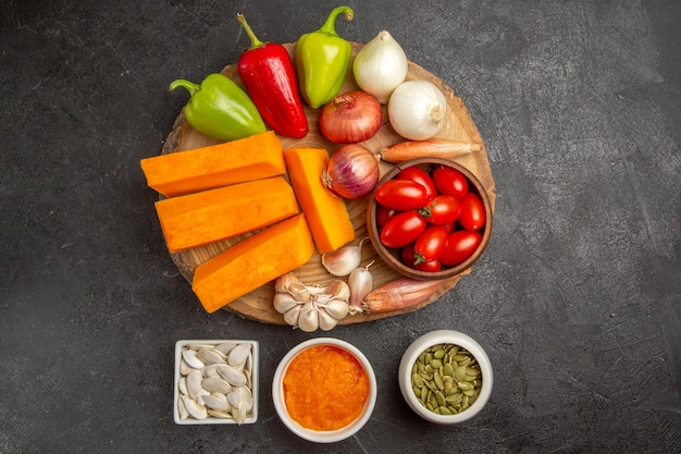 Vue de dessus des légumes frais avec des tranches de citrouille sur la salade mûre de graines fraîches de couleur de fond gris