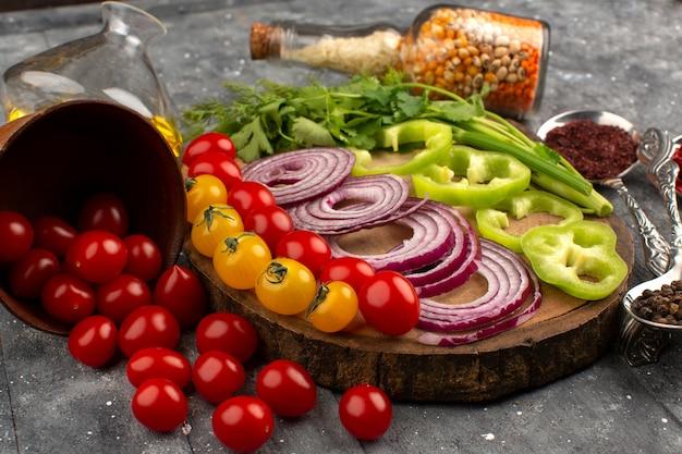 Vue de dessus des légumes frais en tranches comme les oignons, le poivron vert et les tomates sur le gris