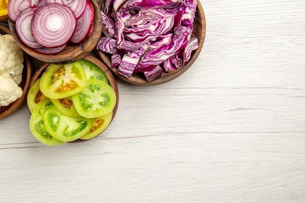 Vue de dessus les légumes hachés coupés chou rouge coupé l'oignon coupé tomates vertes chou-fleur dans des bols sur l'espace libre de table blanche