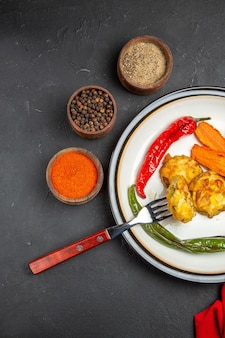 Vue de dessus légumes légumes rôtis à côté des épices de la fourche