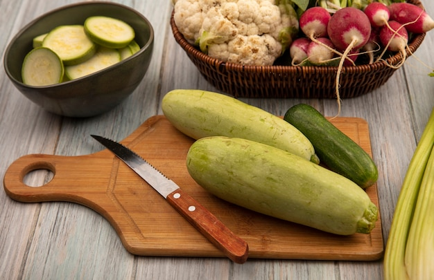 Vue de dessus de légumes sains tels que les courgettes et le concombre sur une planche de cuisine en bois avec un couteau avec des courgettes hachées sur un bol sur un fond en bois gris