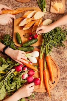 Vue de dessus des légumes sur la table avec des gens qui les préparent