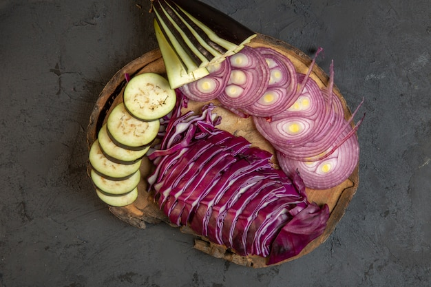 Vue de dessus des légumes en tranches de chou oignon rouge et aubergine sur une planche de bois sur fond noir