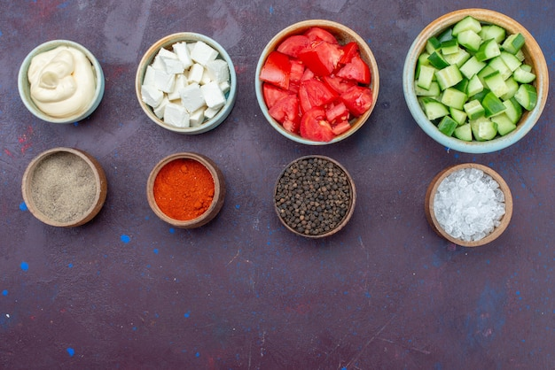 Vue de dessus des légumes tranchés à l'intérieur des bols avec des sauces sur la table sombre salade de légumes repas alimentaire