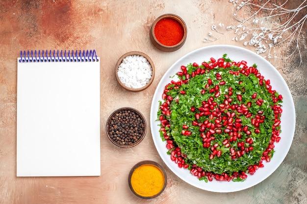 Vue de dessus des légumes verts frais avec des grenades pelées sur un repas au sol clair couleur des fruits vert