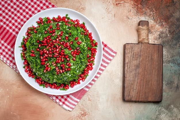 Vue de dessus des légumes verts frais avec des grenades pelées sur un repas vert aux fruits de la table lumineuse