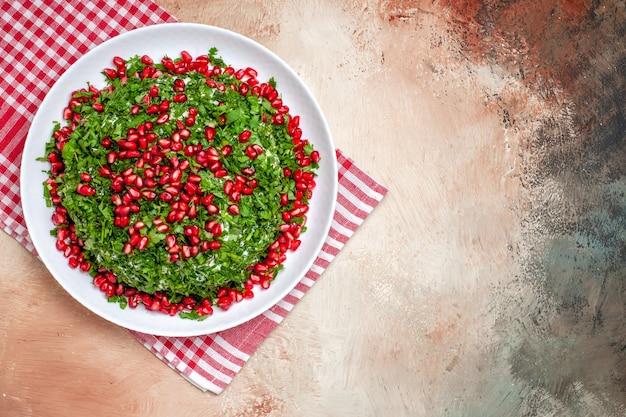 Vue de dessus des légumes verts frais avec des grenades pelées sur une table lumineuse couleur verte