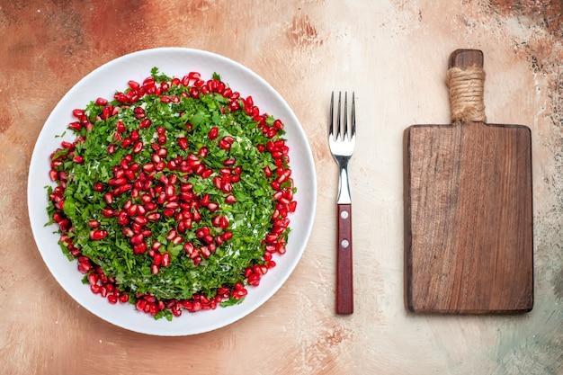 Vue de dessus des légumes verts frais avec des grenades pelées sur la table lumineuse repas couleur des fruits vert