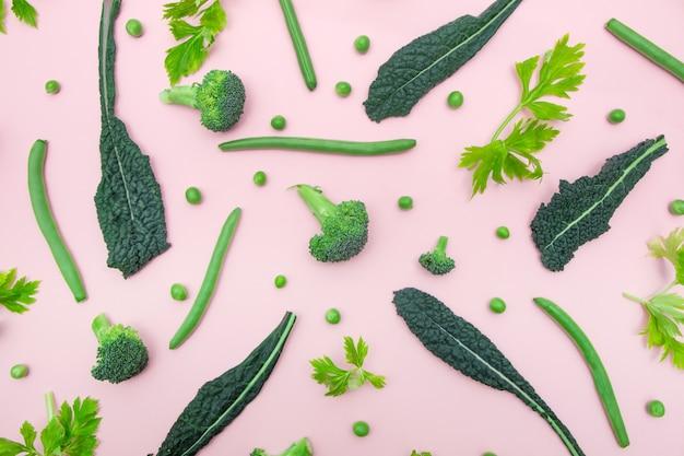 Vue de dessus des légumes verts frais sur la surface de couleur rose