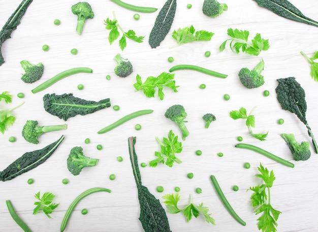 Vue de dessus des légumes verts frais sur la table en bois blanche