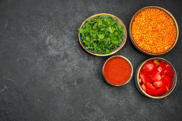 Vue de dessus lentilles lentilles herbes tomates épices dans les bols