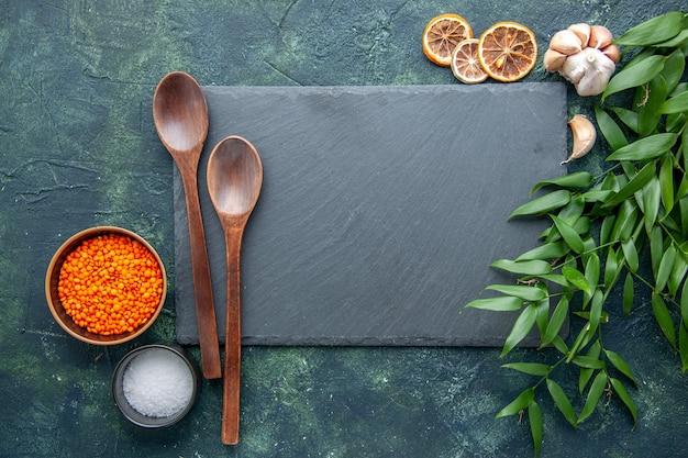 Vue de dessus lentilles orange avec de l'ail et du sel sur fond bleu foncé photo alimentaire piment épicé soupe aux graines forte couleur