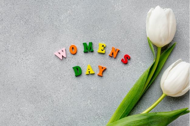 Vue de dessus lettrage de la journée des femmes sur le ciment avec des tulipes blanches