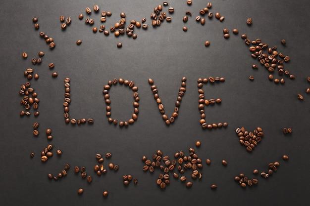 Vue de dessus de la lettre amour, mot fabriqué à partir de grains de café sur fond noir pour la conception