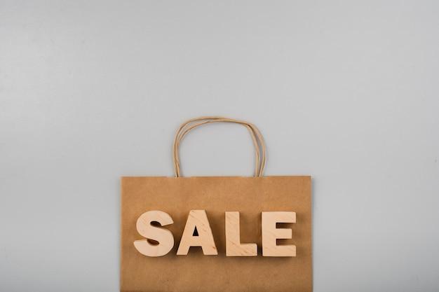 Vue de dessus des lettres de vente avec sac en papier sur fond uni