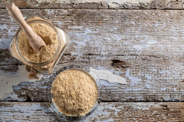 Vue de dessus de la levure nutritionnelle en flocons dans des bocaux en verre sur fond de bois rustique