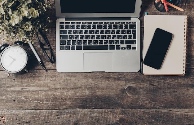 Vue de dessus d'un lieu de travail de bureau à domicile sur une vieille table en bois avec ordinateur portable