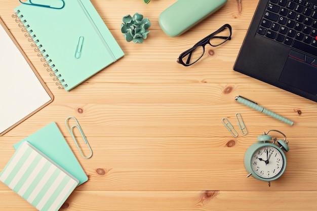 Vue de dessus sur le lieu de travail avec ordinateur portable et fournitures de bureau