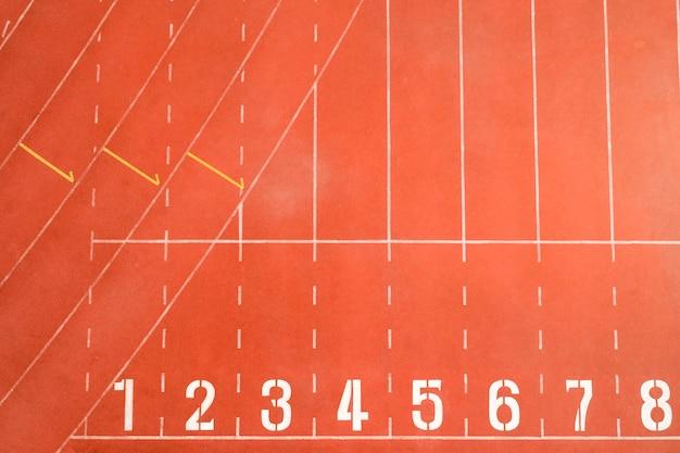 Vue de dessus de la ligne de départ de piste d'athlétisme avec numéros de voie