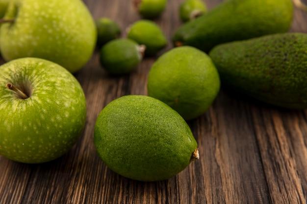 Vue de dessus des limes fraîches avec des pommes vertes et des feijoas isolés sur un fond en bois
