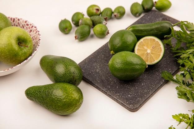 Vue de dessus des limes sur une planche de cuisine avec des feijoas de concombre et des avocats isolés sur un mur blanc