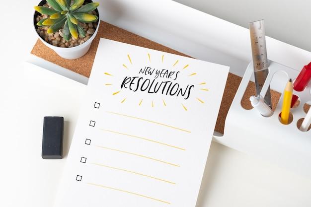 Vue de dessus, liste de contrôle des résolutions du nouvel an sur une note de papier blanc au bureau moderne