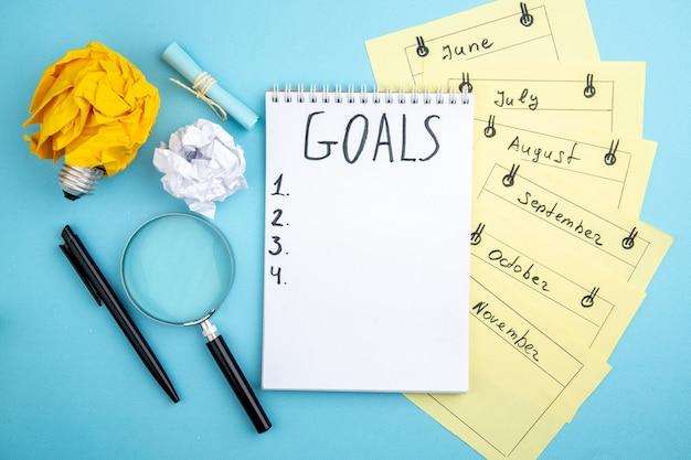 Vue de dessus liste d'objectifs écrite sur le bloc-notes cartes de rappel mensuel stylo lupa papier froissé avec concept d'ampoule idée sur fond bleu