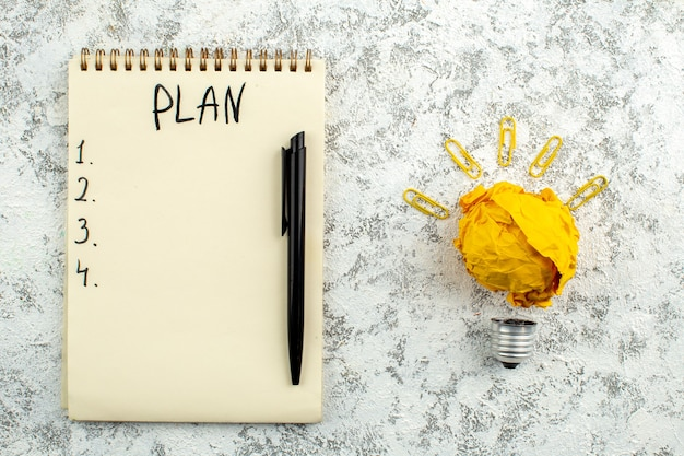 Vue de dessus liste des plans écrite sur ordinateur portable stylo noir idée ampoule concept sur fond gris blanc